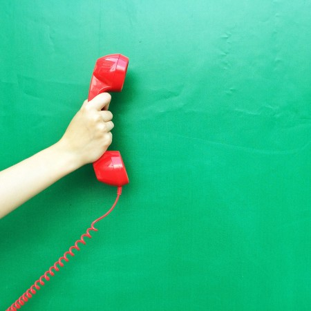 Hand hlt rotes Telefon